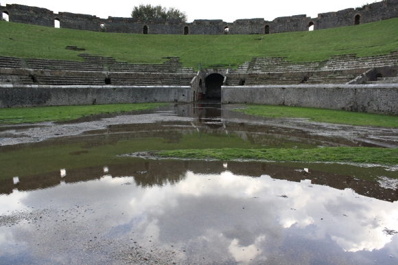An old amphitheater reflected in rain water at Pompeii, Italy